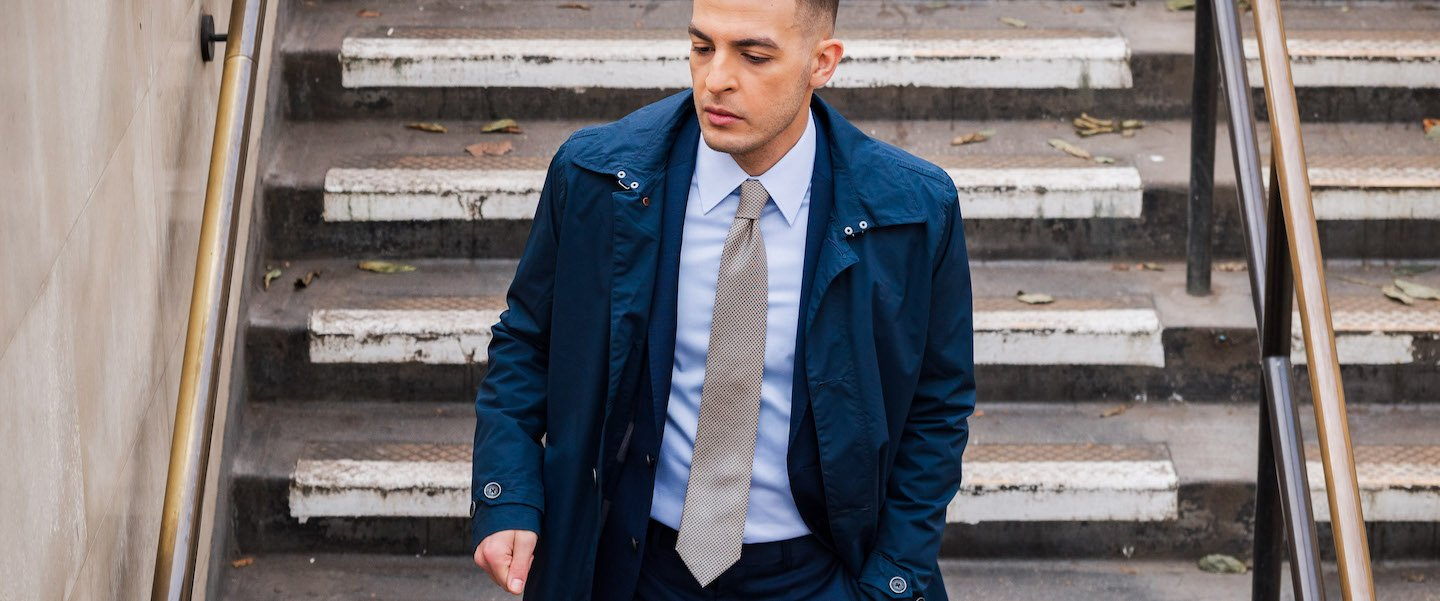 Model wearing men's dress shirt and a suit with a navy jacket on walking down steps in London