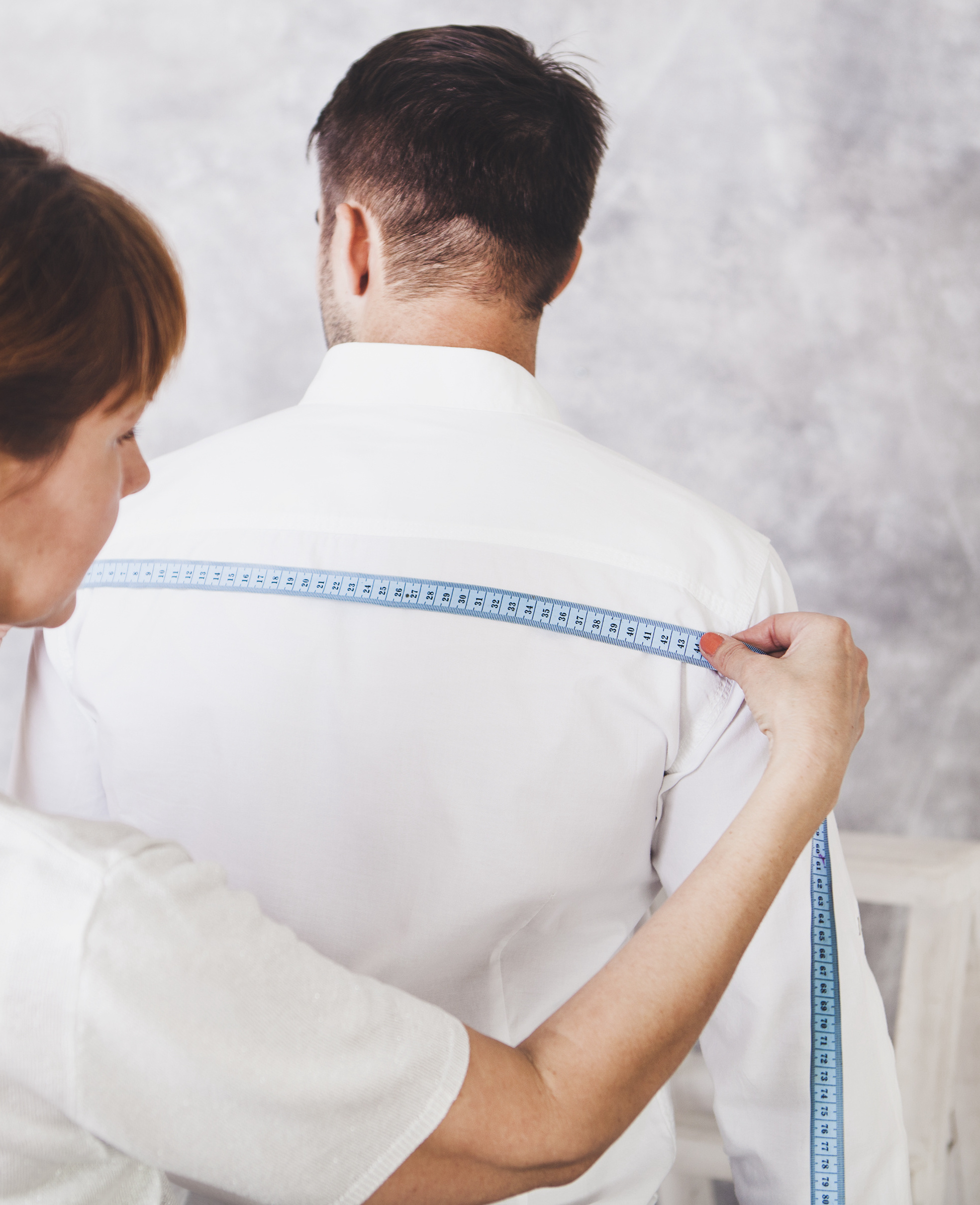 A tailor takes the measurements of the Dress Shirt.