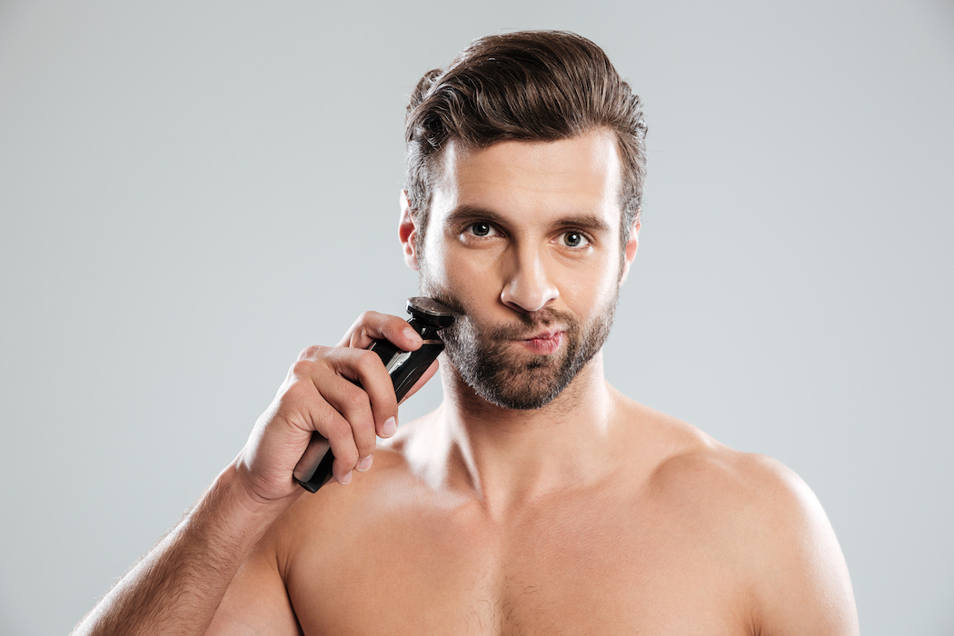 Portrait of a pensive bearded guy looking at electric shaver before his morning habits over a grey background